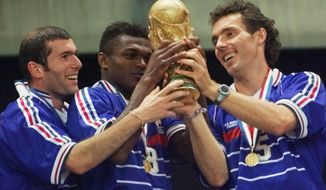 FILE - In this Sunday, July 12, 1998 file photo, France's players from left, Zinedine Zidane, Marcel Desailly and Laurent Blanc hold the soccer World Cup after France defeated Brazil 3-0 in the World Cup final, at the Stade de France in Saint Denis. The 21st World Cup begins on Thursday, June 14, 2018, when host Russia takes on Saudi Arabia. (AP Photo/Michel Euler, file)