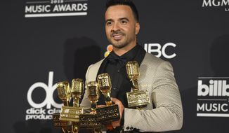 """Luis Fonsi, winner of the awards for hot Latin song of the year, hot Latin song of the year - vocal event, airplay song of the year, digital song of the year, streaming song of the year and Latin pop song of the year for """"Despacito"""" and hot Latin songs artist of the year - male, poses in the press room at the Billboard Music Awards at the MGM Grand Garden Arena on Sunday, May 20, 2018, in Las Vegas. (Photo by Jordan Strauss/Invision/AP)"""