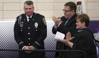 Officer Mark Dallas is honored during graduation ceremonies Sunday, May 20, 2018 at Dixon High School. Dallas is being hailed has a hero for stopping a former student armed with a rifle who attempted to enter the school last week. (Brian Cassella/Chicago Tribune via AP)