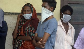 Indians standing in a queue outside a hospital wear masks as a precautionary measure against the Nipah virus at the Government Medical College hospital in Kozhikode, in the southern Indian state of Kerala, Monday, May 21, 2018. The deadly virus has killed at least three people in southern India, officials said Monday, with medical teams dispatched to the area amid reports that up to six other people could have died from the disease and others are ill. (AP Photo)