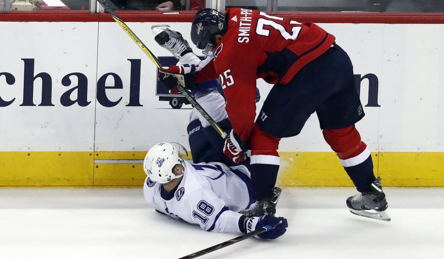 Tampa Bay Lightning left wing Ondrej Palat (18), from the Czech Republic, gets hit by Washington Capitals right wing Devante Smith-Pelly (25) during the second period of Game 6 of the NHL Eastern Conference finals hockey playoff series, Monday, May 21, 2018, in Washington. (AP Photo/Alex Brandon)