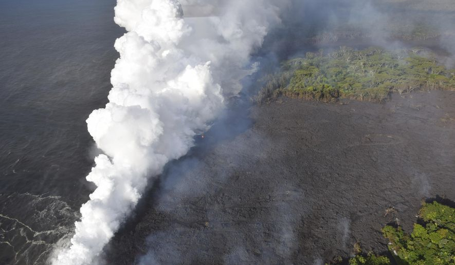 In this image provided by the U.S. Geological Survey, lava from fissure 20 enters the ocean near Pahoa, Hawaii on Sunday, May 20, 2018. The volcano that is oozing, spewing and exploding on Hawaii's Big Island has gotten more hazardous, sending rivers of molten rock pouring into the ocean Sunday and launching lava skyward that caused the first major injury. (U.S. Geological Survey via AP)