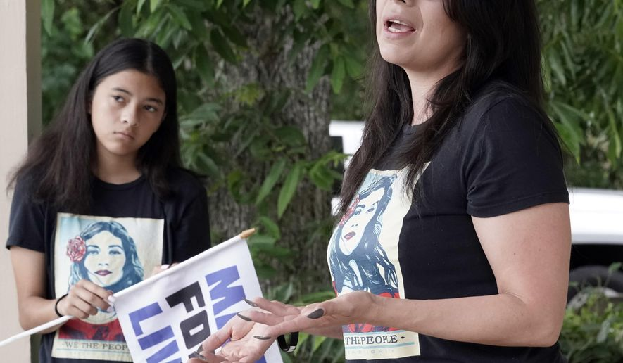 Christina Delgado, right, talks about the school shooting as her daughter, London, listens Sunday, May 20, 2018, in Santa Fe, Texas. Delgado watched in horror last week as the extreme gun violence she had marched to prevent arrived in her town. A gunman opened fire inside Santa Fe High School on Friday, killing 10 people. (AP Photo/David J. Phillip)
