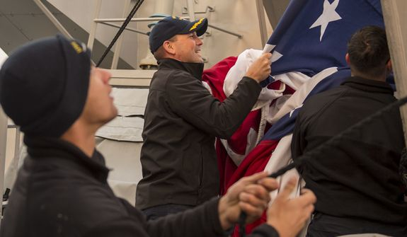 160322-N-GW139-377  WATERS SURROUNDING THE KOREAN PENINSULA (Mar. 22, 2016) - Cmdr. Bryce Benson, executive officer, assists in bringing down the battle ensign on board Arleigh Burke-class guided missile destroyer USS Fitzgerald (DDG 62). Fitzgerald is on patrol in the 7th Fleet area of operations in support of security and stability in the Indo-Asia-Pacific. (U.S. Navy photo by Mass Communication Specialist 3rd Class Eric Coffer/Released) ** FILE **
