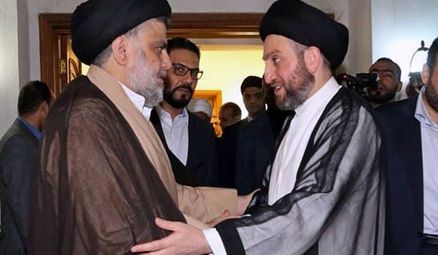 In this photo provided by the Sadr Media Office, Shiite cleric Muqtada al-Sadr, left, greets Shiite leader Ammar al-Hakim on his arrival for their meeting in Baghdad, Iraq, early Tuesday, May 22, 2018. (Sadr Media Office via AP)