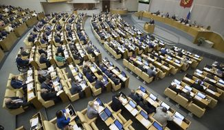 Russian lawmakers work during a session of the State Duma, Russian parliament's lower house in Moscow, Russia, Tuesday, May 22, 2018. Russia's parliament on Tuesday adopted a wide-ranging bill that could freeze crucial exports to the United States and imports to Russia from the U.S. and other countries. (AP Photo/Pavel Golovkin)