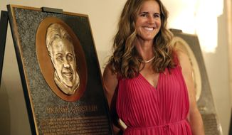 """In this photo taken Monday May 21, 2018, Bay Area Sports Hall of Hame inductee Brandi Chastain poses by her plaque during a press conference in San Francisco. Social media is finding little to like about the likeness on a plaque honoring retired soccer champion Chastain. The Bay Area Sports Hall of Fame in San Francisco unveiled the plaque on Monday night. Chastain diplomatically said """"it's not the most flattering. But it's nice."""" (Scott Strazzante/San Francisco Chronicle via AP)"""