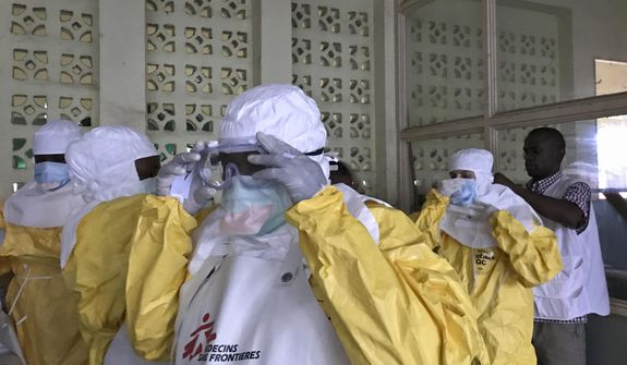 In this photo taken Sunday, May 20, 2018, a team from Medecins Sans Frontieres (Doctors Without Borders) dons protective clothing and equipment as they prepare to treat Ebola patients in an isolation ward of Mbandaka hospital in Congo. Congo's health ministry announced Tuesday, May 22, 2018, six new confirmed cases of the Ebola virus and two new suspected cases while a vaccination effort enters its second day. (Louise Annaud/Medecins Sans Frontieres via AP)