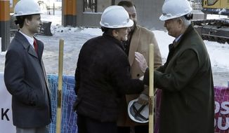 "FILE - In this Dec. 14, 2017 file photo, Quicken Loans founder Dan Gilbert, center, meets with Joe Hudson, former CEO of the J.L. Hudson Company, right, at the groundbreaking site of the city's new 800-foot-tall building, in Detroit. Michigan's economic development board awarded $618 million in tax incentives on Tuesday, May 22, 2018, for a $2.1 billion development project in Detroit that includes a 58-story building on the site of the iconic former J.L. Hudson department store, the first use of new state tax breaks for ""transformational"" redevelopment work. The Strategic Fund board approved the package for Bedrock Management Services, along with a separate $4 million grant for Amazon to locate a warehouse in the Grand Rapids area. (AP Photo/Carlos Osorio File)"