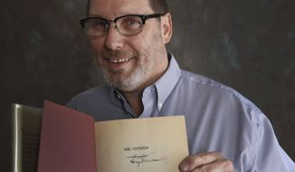 "In this Saturday, May, 19, 2018 photo, Waco ISD social studies specialist Robert Glinski holds a signed copy of Harry S. Truman's 1960 memoir, ""Mr. Citizen"" found last week in the Waco High School's library in Waco, Texas. (Rod Aydelotte/Waco Tribune-Herald via AP)"