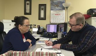 FILE - In this Dec. 6, 2017, file photo, David Ermold, right, files to run for Rowan County Clerk in Kentucky as Clerk Kim Davis look on in Morehead, Ky. Ermold, a gay man in Kentucky, wants to run against the county clerk who denied him a marriage license in 2015. But before Ermold can face Davis at the ballot box, he must first survive a four-person Democratic primary on Tuesday, May 22, 2018. (AP Photo/Adam Beam, File)