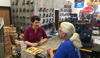 Kentucky 6th Congressional District Democratic candidate Amy McGrath, left, speaks with Vonnie Gesinske at RT Outfitters on Monday, May 21, 2018, in Lexington, Ky. McGrath is one of several candidates seeking the Democratic nomination in Tuesday's primary election for the chance to challenge likely Republican nominee Andy Barr, a three-term incumbent. (AP Photo/Adam Beam)