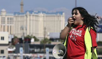 Volunteer Jenifer Murias yells into a megaphone as Culinary Union members file into a university arena to vote on whether to authorize a strike Tuesday, May 22, 2018, in Las Vegas.   A potential strike would affect 34 casino-hotels.A majority yes vote would not immediately affect the casinos, but it would give union negotiators a huge bargaining chip by allowing them to call for a strike at any time starting June 1. (AP Photo/Isaac Brekken)