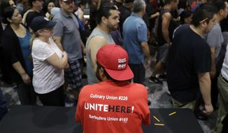 Culinary Union members exit a university arena after voting on whether to authorize a strike Tuesday, May 22, 2018, in Las Vegas.  A potential strike would affect 34 casino-hotels. A majority yes vote would not immediately affect the casinos, but it would give union negotiators a huge bargaining chip by allowing them to call for a strike at any time starting June 1.  (AP Photo/Isaac Brekken)