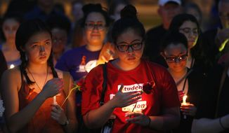 People attend a vigil for the victims of the latest school shooting in Texas, at the Arizona Capitol, Monday, May 21, 2018, in Phoenix. (AP Photo/Ross D. Franklin)
