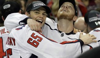 Washington Capitals left wing Andre Burakovsky (65) and defenseman John Carlson celebrate after the Capitals defeated the Tampa Bay Lightning 4-0 during Game 7 of the NHL Eastern Conference finals hockey playoff series Wednesday, May 23, 2018, in Tampa, Fla. (AP Photo/Chris O'Meara)