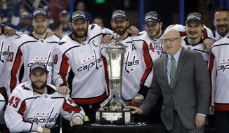 NHL Deputy Commissioner Bill Daly, right, poses with members of the Washington Capitals and the Prince of Wales trophy after the Capitals defeated the Tampa Bay Lightning 4-0 during Game 7 of the NHL Eastern Conference finals hockey playoff series Wednesday, May 23, 2018, in Tampa, Fla. (AP Photo/Chris O'Meara)