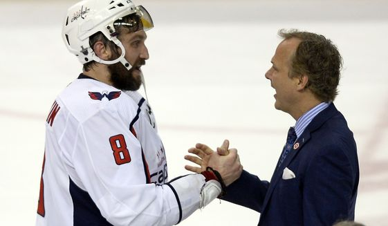 Washington Capitals left wing Alex Ovechkin (8) shakes hands with coach Barry Trotz after the Capitals defeated the Tampa Bay Lightning 4-0 in Game 7 of the NHL Eastern Conference finals hockey playoff series Wednesday, May 23, 2018, in Tampa, Fla. (AP Photo/Jason Behnken)
