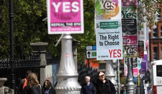 "In this photo taken on May 17, 2018, Pro and anti-abortion poster's on lamppost's outside government buildings in Dublin, Ireland. In homes and pubs, on leaflets and lampposts, debate rages in Ireland over whether to lift the country's decades-old ban on abortion. Pro-repeal banners declare: ""Her choice: vote yes."" Anti-abortion placards warn against a ""license to kill."" Online, the argument is just as charged _ and more shadowy _ as unregulated ads of uncertain origin battle to sway voters ahead of Friday's referendum, which could give Irish women the right to end their pregnancies for the first time.  (AP Photo/Peter Morrison)"