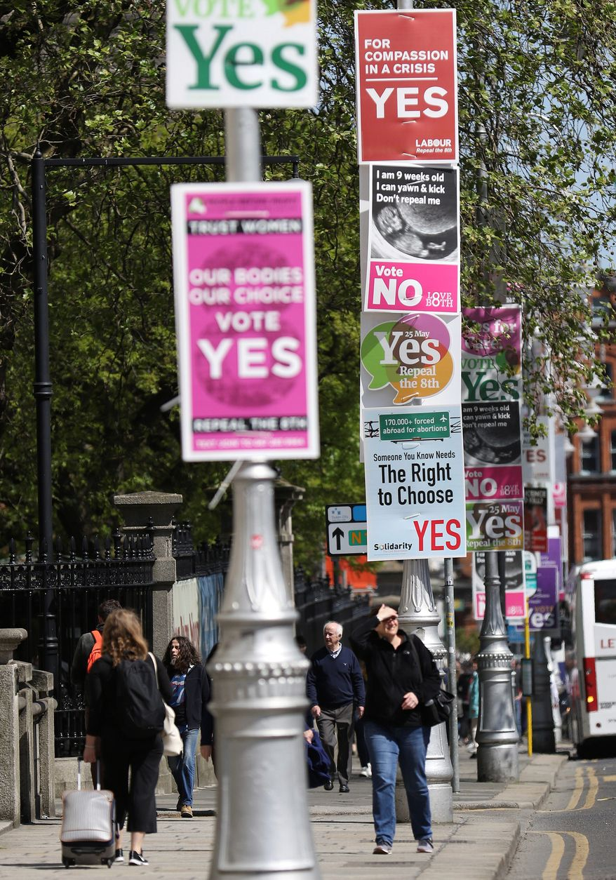 """In this photo taken on May 17, 2018, Pro and anti-abortion poster's on lamppost's outside government buildings in Dublin, Ireland. In homes and pubs, on leaflets and lampposts, debate rages in Ireland over whether to lift the country's decades-old ban on abortion. Pro-repeal banners declare: """"Her choice: vote yes."""" Anti-abortion placards warn against a """"license to kill."""" Online, the argument is just as charged _ and more shadowy _ as unregulated ads of uncertain origin battle to sway voters ahead of Friday's referendum, which could give Irish women the right to end their pregnancies for the first time.  (AP Photo/Peter Morrison)"""