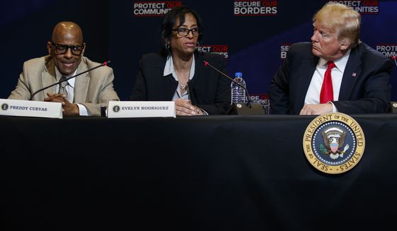 Freddy Cuevas, left, and President Donald Trump listen as Evelyn Rodriguez speaks about the murder of her daughter by the MS-13 street gang during a roundtable on immigration policy at Morrelly Homeland Security Center, Wednesday, May 23, 2018, in Bethpage, N.Y. (AP Photo/Evan Vucci)