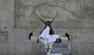 In this Sunday, April 1, 2018, photo members of the Presidential Guard perform in front of the Tomb of the Unknown Soldier in Athens. Created 150 years ago as a fighting force that distinguished itself in a series of wars, the unit is now purely ceremonial in function, codifying in its dress and routine a popular conception of Greekness that evolved since the modern Greek state was formed nearly two centuries ago. (AP Photo/Thanassis Stavrakis)