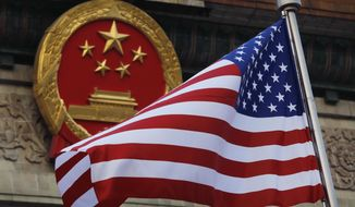 FILE - In this Nov. 9, 2017, file photo, an American flag is flown next to the Chinese national emblem during a welcome ceremony for visiting U.S. President Donald Trump outside the Great Hall of the People in Beijing. The State Department said an email notice Wednesday, May 23, 2018, that a U.S. government employee in southern China reported abnormal sensations of sound and pressure, recalling similar experiences among American diplomats in Cuba who later fell ill. (AP Photo/Andy Wong, File)