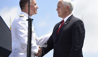 Vice President Mike Pence, right, shakes hands with Admiral Paul F. Zukunft, USCA, at the commencement for the United States Coast Guard Academy in New London, Conn., Wednesday, May 23, 2018. (AP Photo/Jessica Hill)