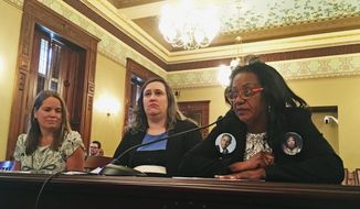 CORRECTS TO HAZEL CREST, NOT CHICAGO - Delphine Cherry, of Hazel Crest, Ill., right, who lost her daughter, Tyese Abney, in 1992, and her son, Tyler Randolph, in 2012, in separate incidents of gun violence, testifies before the House Judiciary-Criminal Committee on Wednesday, May 23, 2018, in Springfield, Ill., against Gov. Bruce Rauner's amendatory veto of legislation to extend the gun-delivery waiting period of all guns to 72 hours. (AP Photo/John O'Connor)