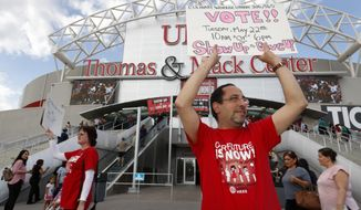 Union organizers Angie Qin, left, and David Saba hold signs as members of the Culinary Workers Union, Local 226, file into a university arena to vote on whether to authorize a strike Tuesday, May 22, 2018, in Las Vegas. A potential strike would affect 34 casino-hotels. A majority yes vote would not immediately affect the casinos, but it would give union negotiators a huge bargaining chip by allowing them to call for a strike at any time starting June 1. (Steve Marcus/Las Vegas Sun via AP)