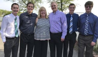 In this May 16, 2018 photo provided by the Doyle family, 19-year-old quadruplets Patrick, from left, Nick, mother Chris, father Rick, Matt and Tony Doyle pose in Manitou Beach, Mich. Defying biological and statistical odds, a set of quadruplets will join one of the largest freshman classes in Michigan State University history in August of 2018. The brothers plan on pairing up in adjoining dorm rooms. (Cindy Fromme/Doyle Family via AP)