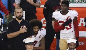 """In this Thursday, Sept. 1, 2016, file photo, San Francisco 49ers quarterback Colin Kaepernick, middle, kneels during the national anthem before the team's NFL preseason football game against the San Diego Chargers, in San Diego. NFL owners have approved a new policy aimed at addressing the firestorm over national anthem protests, permitting players to stay in the locker room during the """"The Star-Spangled Banner"""" but requiring them to stand if they come to the field. The decision was announced Wednesday, May 23, 2018,  by NFL Commissioner Roger Goodell during the league's spring meeting in Atlanta.(AP Photo/Chris Carlson, File)"""