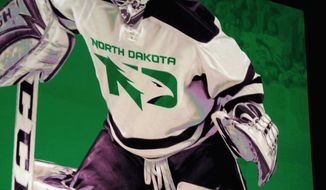 FILE - In this June 22, 2016, file photo, a photo of a mock hockey jersey with the new University of North Dakota Fighting Hawks logo is seen at an unveiling ceremony in Grand Forks, N.D. A dispute between the university and one of its most generous benefactors over painting its logo on an arena floor is underscoring the difficulty the school has had in building acceptance of its nickname. (AP Photo/Dave Kolpack, File)
