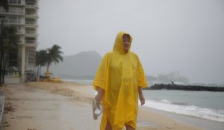 File - In this Oct. 19, 2014, file photo, Maryanne Fisher, of League City, Texas, stands in the rain on Waikiki Beach with Diamond Head in the background in Honolulu as Hurricane Ana brought a steady rain to the Hawaiian Island of Oahu as it passed about 180 miles west. On Wednesday, May 23, 2018, NOAA's Central Pacific Hurricane Center announces the hurricane season outlook for 2018. (AP Photo/P. Solomon Banda, File)