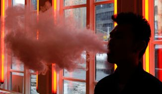 FILE - In this Feb. 20, 2014 file photo, a customer exhales vapor from an e-cigarette at a store in New York. In a large study of company wellness programs released on Wednesday, May 23, 2018, e-cigarettes worked no better than traditional stop-smoking tools, and the only thing that really helped was paying folks to kick the habit. (AP Photo/Frank Franklin II, File)