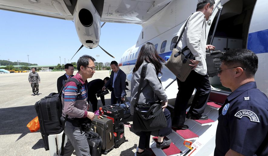 South Korean journalists board a plane to leave for North Korea, at Seoul Airport in Seongnam, South Korea, Wednesday, May 23, 2018. Eight journalists from South Korea departed for rival North Korea on Wednesday after the North allowed them to join the small group of foreign media in the country to witness the dismantling of its nuclear test site this week, Seoul officials said. (Yonhap via AP)