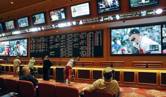 """FILE – In this May 14, 2018, file photo, people make bets in the sports book at the South Point hotel and casino in Las Vegas. A top New Jersey lawmaker, Democratic state Senate President Steve Sweeney, urged all 50 states on Wednesday, May 23, 2018, to reject """"integrity fee"""" payments to professional sports leagues in any sports betting legislation, calling it """"extortion"""" for leagues to demand money for hosting honest games. (AP Photo/John Locher, File) **FILE**"""