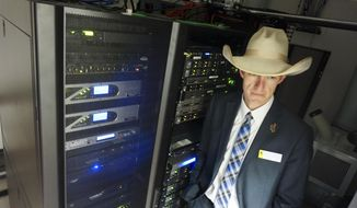 In this March 8, 2018, photo Wyoming state Rep. Tyler Lindholm poses next to computer servers in an office building in Cheyenne, Wyo. Lindholm was a lead proponent of several new laws that have made Wyoming friendly to the networked ledgering technology called blockchain. Supporters say that by welcoming blockchain, the technology underlying cryptocurrencies including bitcoin, Wyoming has become a good place for tech business. (AP Photo/Mead Gruver)