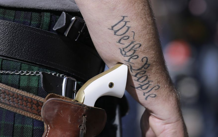 FILE - In this Jan. 26, 2015 file photo, a supporter of open carry gun laws, wears a pistol as he prepares for a rally in support of open carry gun laws at the Capitol, in Austin, Texas. Texas is still sorting out where firearms are allowed, and where they're not, more than a year after Republican Gov. Greg Abbott signed a suite of laws that vastly expanded gun rights. (AP Photo/Eric Gay, File)