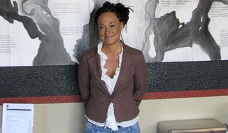 In this July 24, 2009, file photo, Rachel Dolezal, a leader of the Human Rights Education Institute, stands in front of a mural she painted at the institute's offices in Coeur d'Alene, Idaho. (AP Photo/Nicholas K. Geranios, File)