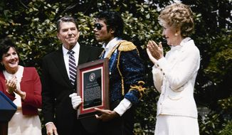 Michael Jackson stands with President and Nancy Reagan May 14, 1984 on the south lawn of the White House prior to receiving an award from the president for his contribution to the drunk driving awareness program. (AP Photo/Scott Stewart)