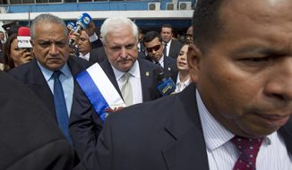 FILE.- In this Jan. 2, 2014 file photo, Panama's then President Ricardo Martinelli, center, leaves Congress after delivering his last State of the Nation address, in Panama City. A spokesman for Martinelli said Thursday, May 24, 2018, the ex-leader is dropping his legal efforts to fight extradition from the United States to Panama, confirming that Martinelli shared his decision through a handwritten note from jail in Miami. (AP Photo/Arnulfo Franco, File)
