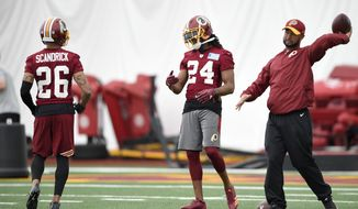 Washington Redskins defensive back Josh Norman (24) stands next to Washington Redskins defensive back Orlando Scandrick (26) during an NFL football team practice, Wednesday, May 23, 2018, in Ashburn, Va. (AP Photo/Nick Wass)
