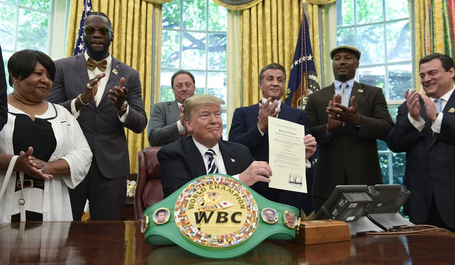 President Donald Trump center, posthumous pardons Jack Johnson, boxing's first black heavyweight champion, during an event in the Oval Office of the White House in Washington, Thursday, May 24, 2018. Trump is joined by, from left, Linda Haywood, who is Johnson's great-great niece, heavyweight champion Deontay Wilder, Keith Frankel, Sylvester Stallone, former heavyweight champion Lennox Lewis, and World Boxing Council President Mauricio Sulaiman Saldivar. (AP Photo/Susan Walsh)