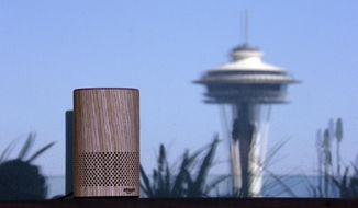 """FILE - In this Sept. 27, 2017, file photo, an Amazon Echo device sits on a balcony outside an Amazon office as the Space Needle is reflected in windows behind it following a program announcing several new Amazon products by the company, in Seattle. Amazon says an """"unlikely"""" string of events prompted its Echo personal assistant device to record a Portland, Ore., family's private conversation and then send the recording to an acquaintance in Seattle. (AP Photo/Elaine Thompson, File)"""