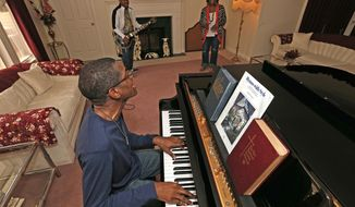 In this May 10, 2018 photo, Christopher Pleasant plays a Backstreet Boys song accompanied  by his brother Jason on guitar as his mom Gwendolyn's dances in the living room of their home in Quincy, Ill. Both Jason and Christopher are autistic and have found creative and religious outlets in Quincy.(Jake Shane/The Quincy Herald-Whig via AP)