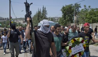 A masked gunman shoots in the air during the funeral of Palestinian Uday Abu Khalil, 15, who died from his wounds sustained in clashes with Israeli troops during during protests last week, in the West village of Ein Senia, near Ramallah, Thursday, May 24, 2018. (AP Photo/Nasser Nasser)