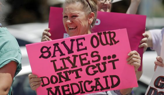 In this June 27, 2017, file photo, protesters block a street during a demonstration against the Republican bill in the U.S. Senate to replace former President Barack Obama's health care law, in Salt Lake City. Utah lawmakers are expressing concern about the possibility that voters could expand Medicaid after years of debate at the legislature. (AP Photo/Rick Bowmer, File)