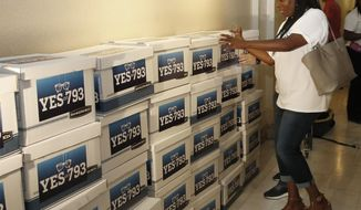 Shwanda Clark, with Oklahomans for Consumer Freedom, helps to stack empty boxes representing petitions in their petition drive outside the Secretary of State's office in Oklahoma City, Thursday, May 24, 2018. The group is seeking a public vote on whether to allow optometrists to operate inside retail establishments and says they've gathered enough signatures to place the measure on the November ballot. (AP Photo/Sue Ogrocki)