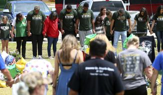 Houston Texans players join in a prayer circle at a memorial for the Santa Fe High School shooting victims outside the school Wednesday, May 23, 2018, in Santa Fe, Texas. ( Godofredo A. Vasquez /Houston Chronicle via AP)